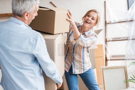 happy senior couple holding cardboard boxes while moving home