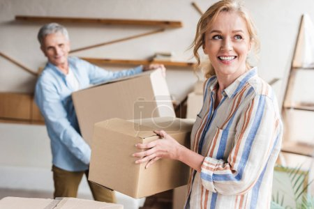 happy elderly couple holding cardboard boxes while moving home