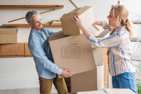 side view of happy elderly couple holding cardboard boxes while moving home