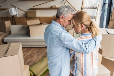 back view of upset senior couple embracing while standing between cardboard boxes during relocation