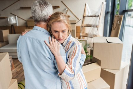 high angle view of pensive senior couple hugging while moving home