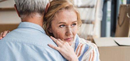 Foto de Foto recortada de senior hombre a mujer pensativa abrazando mientras se mueve Inicio - Imagen libre de derechos
