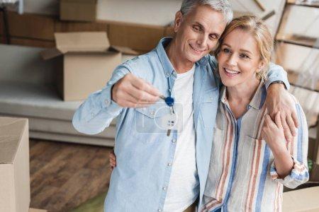 Foto de Vista de ángulo alto de la feliz pareja de ancianos sosteniendo las llaves de nuevo nome durante traslado - Imagen libre de derechos