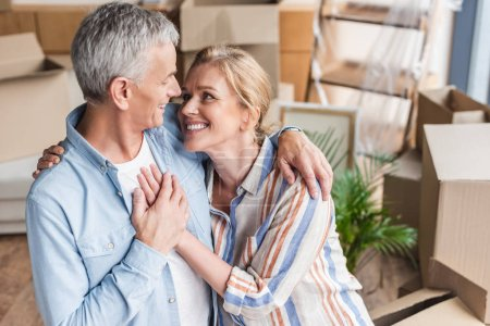 Photo for High angle view of happy senior couple embracing, holding hands and smiling each other in new home - Royalty Free Image