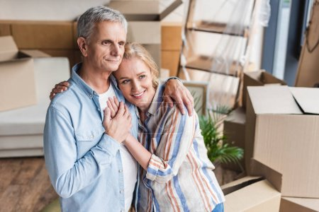 high angle view of happy senior couple embracing and holding hands while moving home