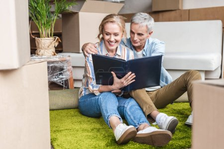 happy senior couple looking at photo album while sitting on carpet in new house