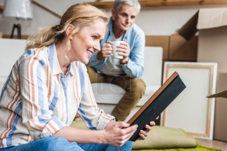 smiling elderly woman holding photo album while relocating with husband in new apartment