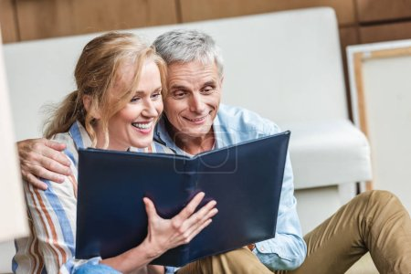 beautiful happy elderly couple looking at photo album together
