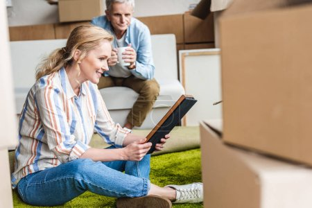 happy elderly woman holding photo album while relocating with husband in new house