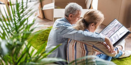high angle view of senior couple looking at photo album during relocation in new house