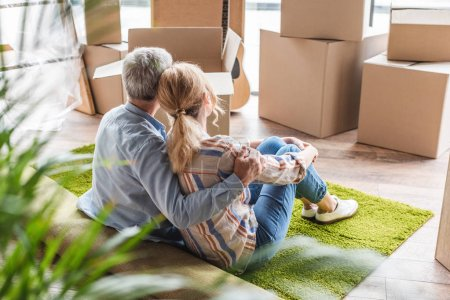 Photo for Back view of elderly couple embracing while sitting on carpet during relocation in new house - Royalty Free Image
