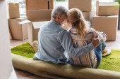 back view of happy senior couple hugging while sitting on carpet in new home