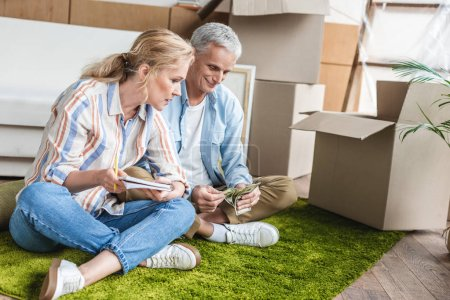 focused senior couple sitting on carpet and counting money during relocation