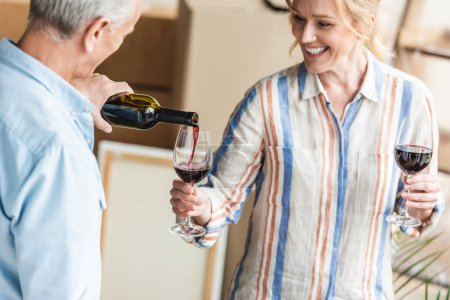 cropped shot of grey hair man pouring wine to happy wife while relocating in new house