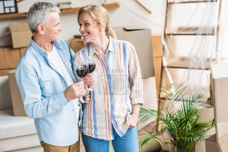 Photo for Happy senior couple holding glasses of wine and smiling each other during relocation - Royalty Free Image