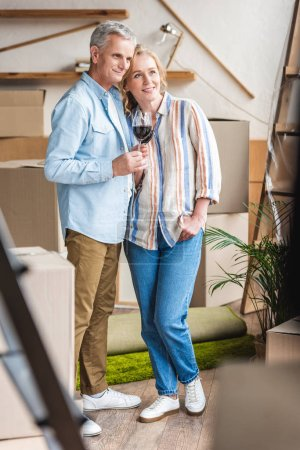 happy senior couple holding glasses of wine and looking away while moving home