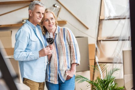 happy elderly couple holding glasses of wine and looking away while moving home