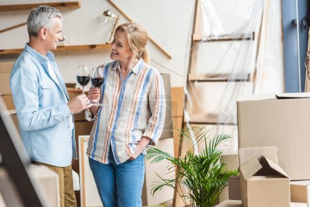 happy elderly couple holding glasses of wine and smiling each other during relocation