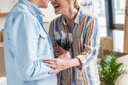cropped shot of happy elderly couple drinking wine together in new house