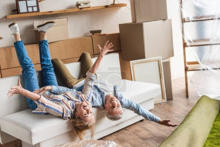 excited elderly couple lying on couch during relocation in new house