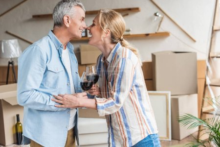 side view of happy senior couple drinking wine during relocation in new house