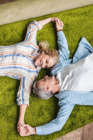 Photo for Top view of happy elderly couple lying together on carpet and holding hands during relocation - Royalty Free Image