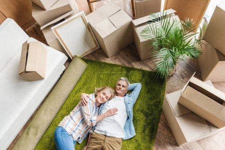 high angle view of happy senior couple lying on carpet while moving home