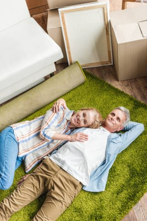 high angle view of happy senior couple lying on carpet in new home