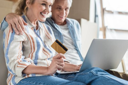 cropped shot of happy senior couple using laptop and holding credit card