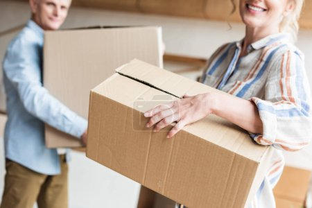 cropped shot of elderly couple holding cardboard boxes and moving home
