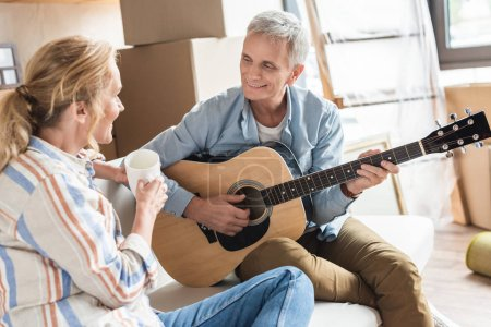 happy grey hair man playing guitar and looking at beautiful wife during relocation