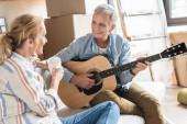 homme heureux cheveux gris jouer de la guitare et en regardant belle femme au cours de la réinstallation