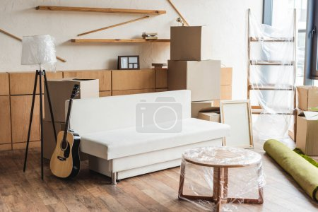 cardboard boxes, rolled carpet, guitar and furniture in new apartment during relocation