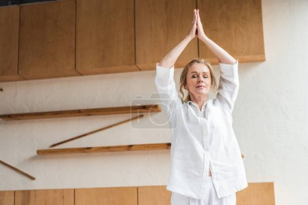 beautiful mature woman with closed eyes practicing yoga