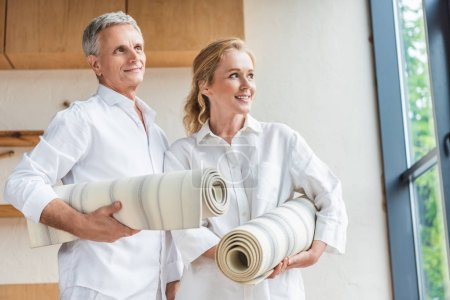 happy senior couple holding yoga mats and looking away