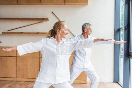 happy elderly couple practicing yoga together