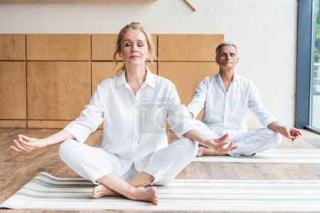 elderly couple sitting in lotus position and meditating together on yoga mats
