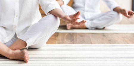 cropped shot of elderly couple sitting in lotus position and practicing yoga together