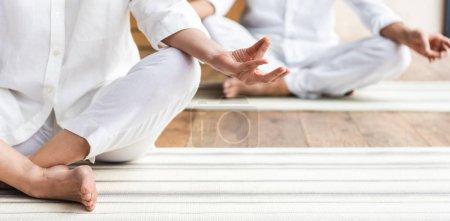 Photo pour Recadrée coup de vieux couple assis en position du lotus et pratiquant d'yoga - image libre de droit