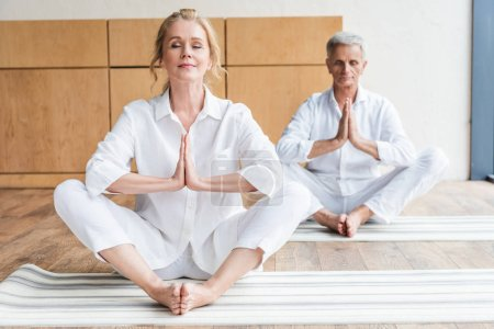elderly couple performing namaste gesture and meditating together on yoga mats