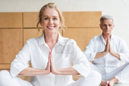 Photo for Beautiful elderly woman performing namaste gesture and smiling at camera while practicing yoga with husband - Royalty Free Image