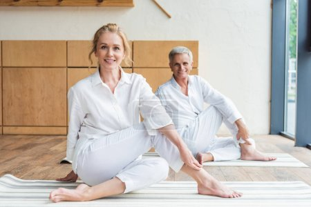 happy senior couple practicing yoga and smiling at camera
