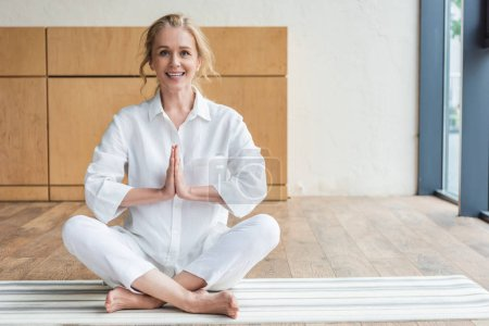 happy mature woman sitting in lotus position with namaste gesture and smiling at camera