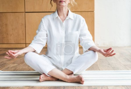 cropped shot of mature woman meditating in lotus position