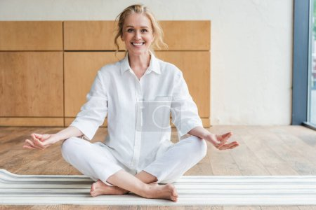happy mature woman sitting in lotus position and smiling at camera