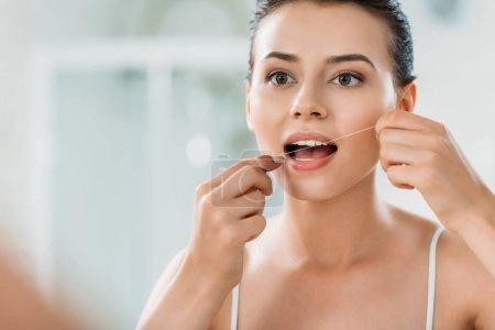 beautiful young woman using dental floss in bathroom