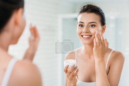 beautiful happy girl applying face cream and looking at mirror in bathroom