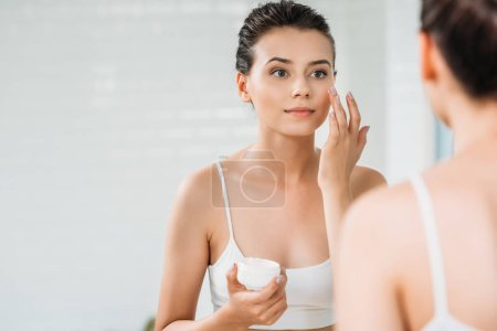 Photo for Beautiful girl applying face cream and looking at mirror in bathroom - Royalty Free Image