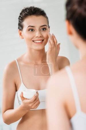 beautiful smiling young woman applying face cream and looking at mirror in bathroom