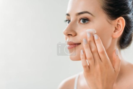 Photo for Beautiful smiling young woman applying face cream and looking away - Royalty Free Image